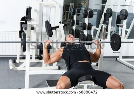 young bodybuilder training in the gym: chest - barbell incline bench press - wide grip - stock photo