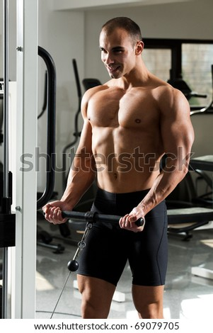 young bodybuilder training in the gym - standing biceps cable curl - stock photo