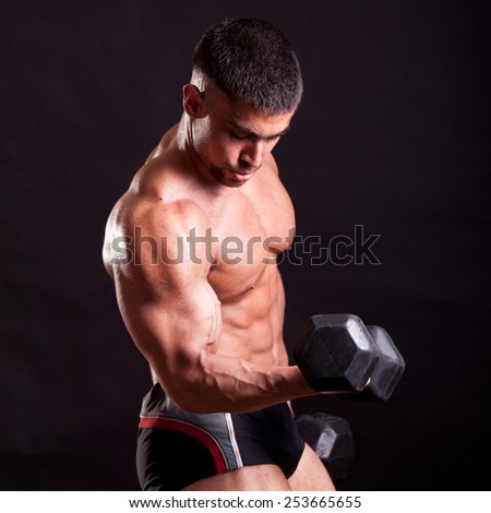 young bodybuilder training over black background - stock photo