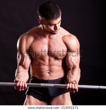 young bodybuilder traininig over balck background - stock photo