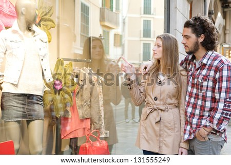 Young bohemian couple looking at clothes in a store window while on vacations in a destination city, pointing at a variety of items. - stock photo