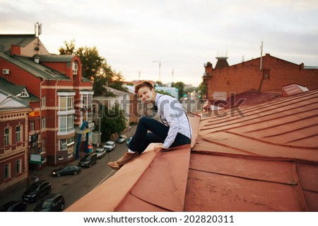Young bold girl woman in hipster clothes, sit on edge of roof, dressed like a boy man in shirt, bow-tie, suspenders and pants trousers on background of city, road and jam - stock photo