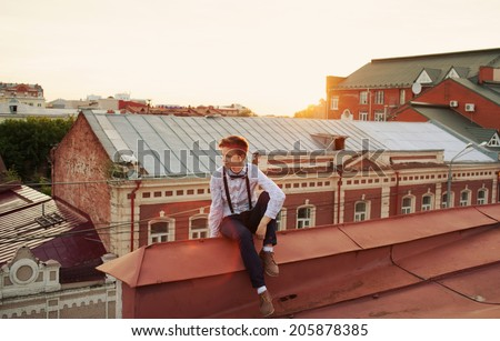 Young bold girl woman in hipster clothes, sit on edge of roof, dressed like a boy man in shirt, bow-tie, suspenders and pants trousers - stock photo