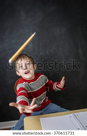 Young bored boy throwing his pencil in the air - stock photo