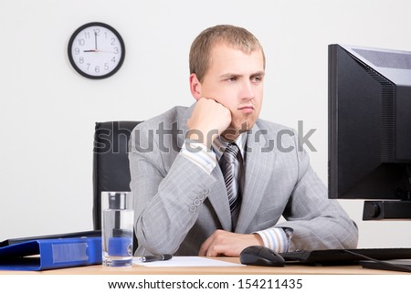 young bored businessman sitting in his office - stock photo