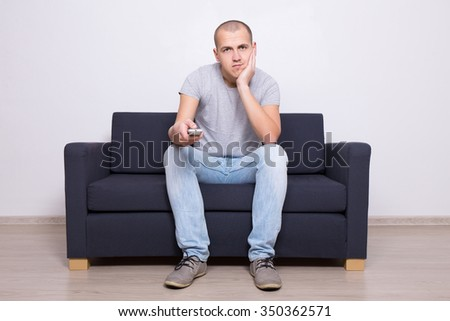 young bored man sitting on sofa and watching tv at home - stock photo