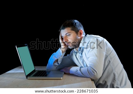 young boring businessman working with computer laptop in frustration, depression, work stress problems and despair concept isolated on black background - stock photo