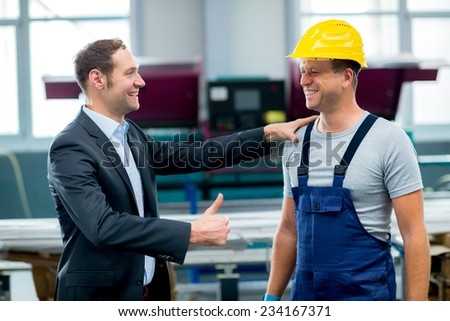 young boss and worker in factory - stock photo