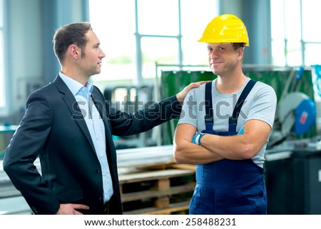 young boss and worker together in factory - stock photo