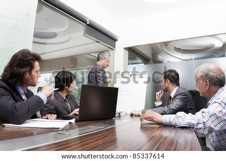 young boss giving presentation to his business team - stock photo