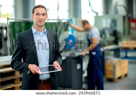 young boss with worker in the background in his factory - stock photo