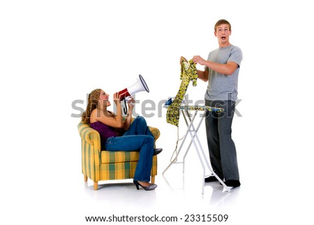 Young bossy woman shouting with megaphone to husband ironing clothing. Studio, white background.