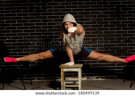 Young boxer doing the splits and punching the air with his fist as he balances across three stools during training to strengthen his muscles and improve suppleness - stock photo