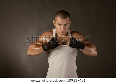 Young Boxer fighter over black, shirt rip to shreds - stock photo