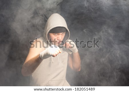 Young boxer fighting in a dark smoke filled atmosphere standing with his fists raised at the ready and a grim intense expression of determination, with copyspace - stock photo