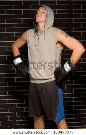 Young boxer gathering his concentration before a fight standing with his gloved hands on his hips and eyes closed with his head tilted back - stock photo