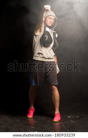 Young boxer giving a power salute punching the air with his bandaged hand as he stands in a smoky atmosphere with his gloves around his neck - stock photo