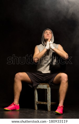 Young boxer praying fervently for a win as he sits waiting on a wooden stool for the start of his match clasping his hands and lifting his eyes to heaven
