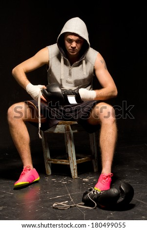 Young boxer sitting on a stool at the side of a ring during training putting on his gloves - stock photo