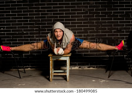 Young boxer stretching and strengthening his leg muscles balancing across three stools with his legs extended in the splits position as he works out during a training session - stock photo