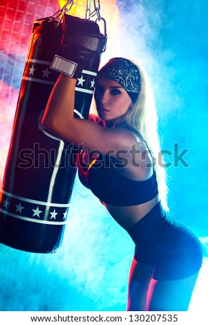 Young boxer woman portrait. Blue and red colors.