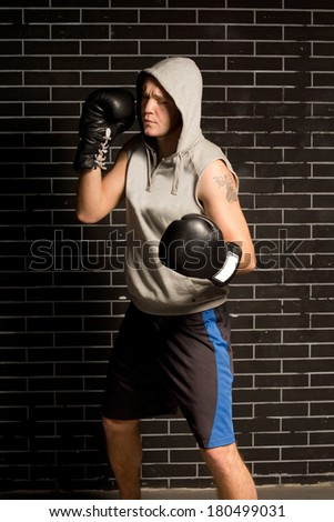Young boxer working out during training standing in front of a dark brick wall with his gloved fists raised and a look of concentration on his face - stock photo