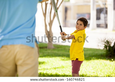 Young boy about to swing a bat while playing baseball with his father - stock photo