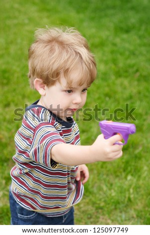 Young boy aiming a  water gun - stock photo