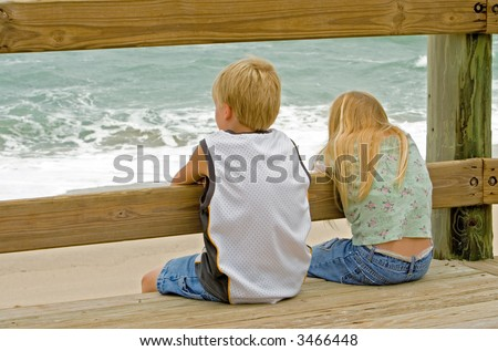 Young boy and girl (brother and sister) watching the ocean waves from the boardwalk - stock photo