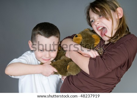 Young boy and girl fighting over toy bear - stock photo