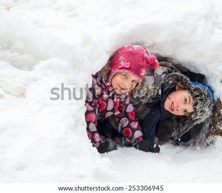 Young boy and girl hiding in a snow cave they made - stock photo