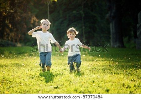 Young boy and girl holding hands and running in a sunny meadow. - stock photo