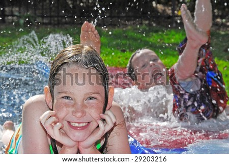 Young boy and girl in outdoor waterplay on slippery slide - stock photo