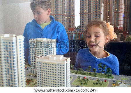 Young boy and girl looking at the layout of the area with housing through the glass, focus on layout. - stock photo