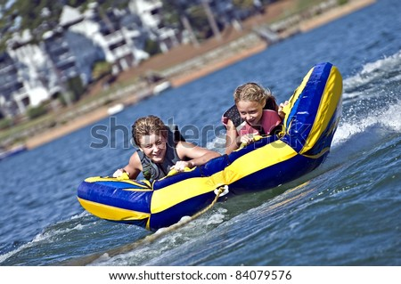 Young boy and girl on a tube behind a boat. - stock photo