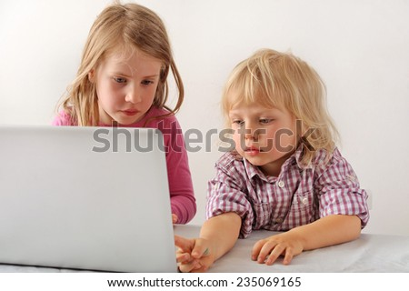 Young boy and girl playing a computer game together, The boy is pointing at the screen - stock photo