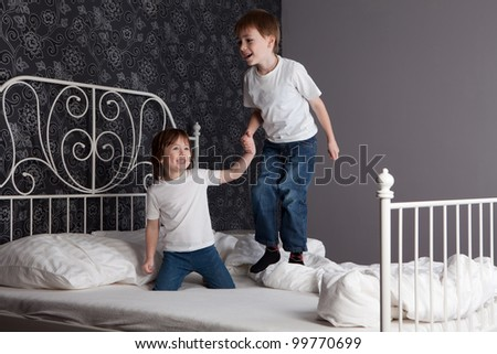 Young boy and girl playing and jumping on a bed. - stock photo