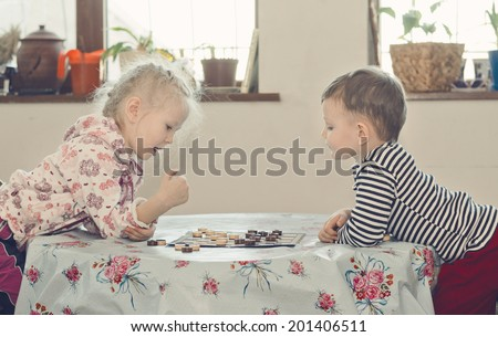 Young boy and girl playing checkers or draughts both leaning over the table looking at the board as they plan their next move - stock photo