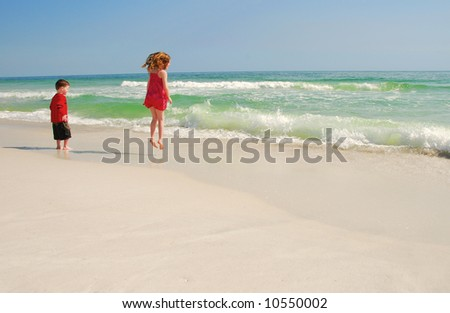 Young boy and girl playing happily at beach - stock photo