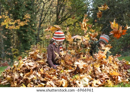 Young boy and girl playing in pile of leaves - stock photo