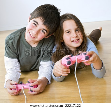 young boy and girl playing with playstation together - stock photo