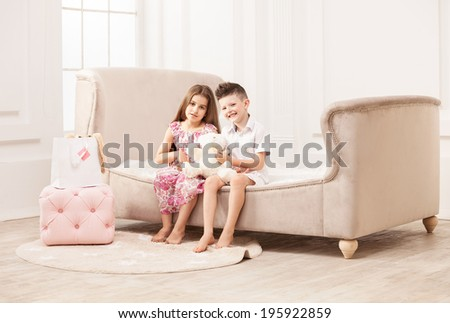 Young boy and girl playing with teddy bear while sitting on couch - stock photo