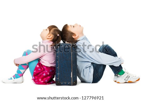 Young boy and girl sitting back to back against a suitcase their eyes shut  with  tiredness and boredom. - stock photo