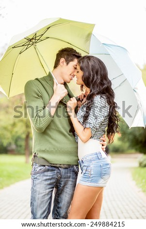 Young boy and girl standing embracing under umbrellas and they kiss. - stock photo