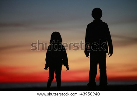 Young Boy and Girl Standing in Silhouette against colorful Sunset - stock photo