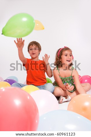 Young boy and girl with colourful balloons - stock photo