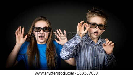 Young boy and girl with 3D glasses.  Movie theater spectators. - stock photo