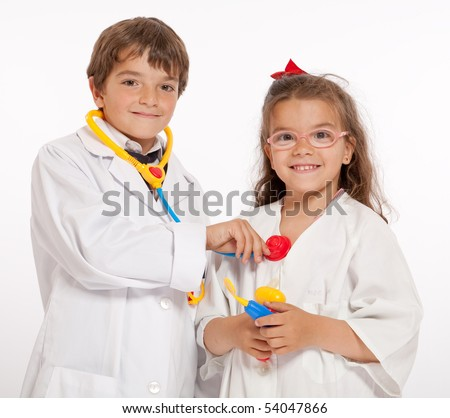 Young boy and girl with medical uniforms and toy doctor instruments - stock photo