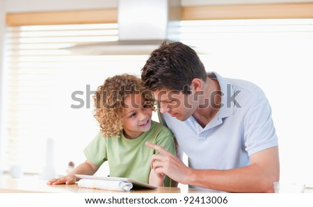 Young boy and his father using a tablet computer in their kitchen - stock photo