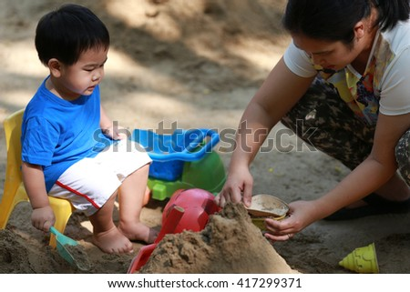 Young boy and his mother are playing with sand box on playground - stock photo